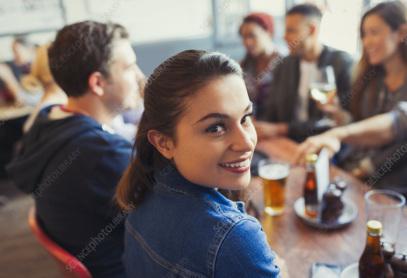 Portrait Woman drinking beer with friends in bar