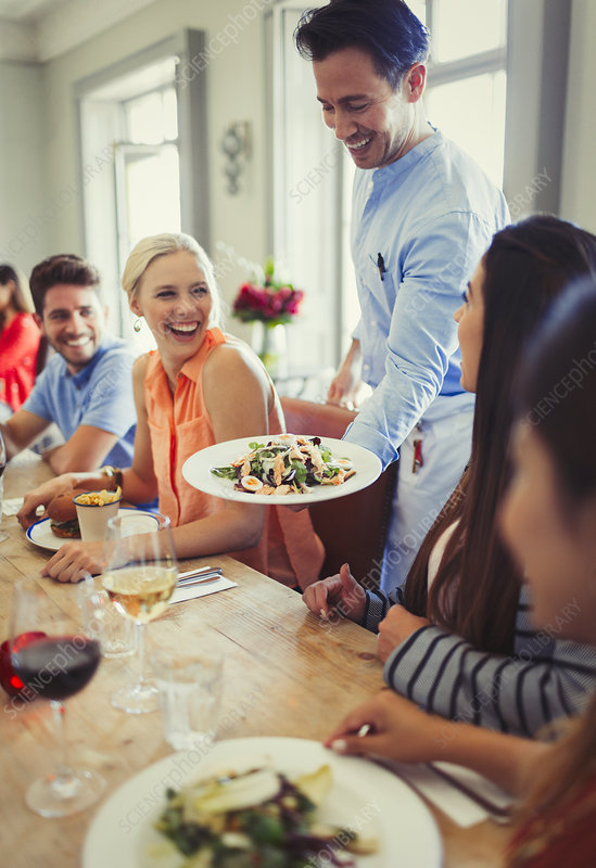 Waiter serving salad to woman dining with friends