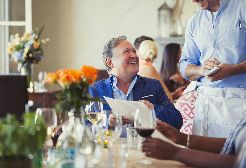 Man with menu ordering from waiter