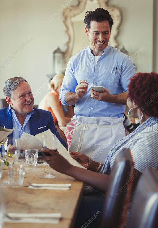 Waiter taking order from couple with menus