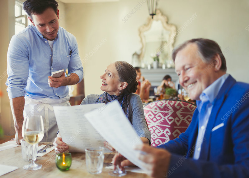 Waiter taking order from senior couple with menus