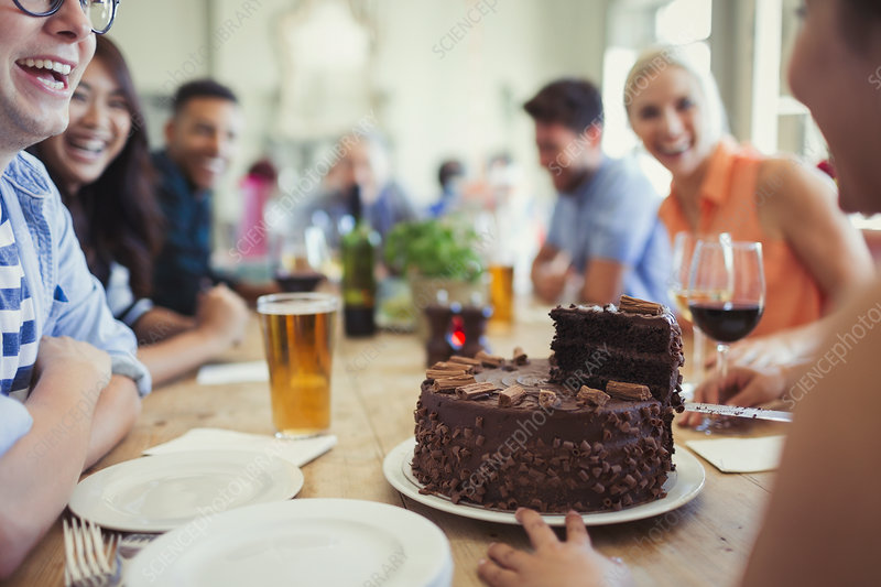 Woman serving chocolate birthday cake to friends