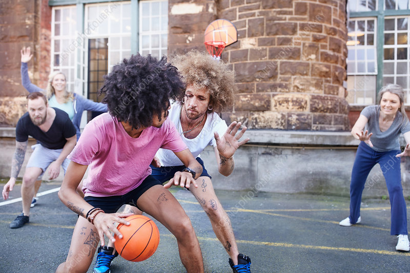 Friends playing basketball on basketball court
