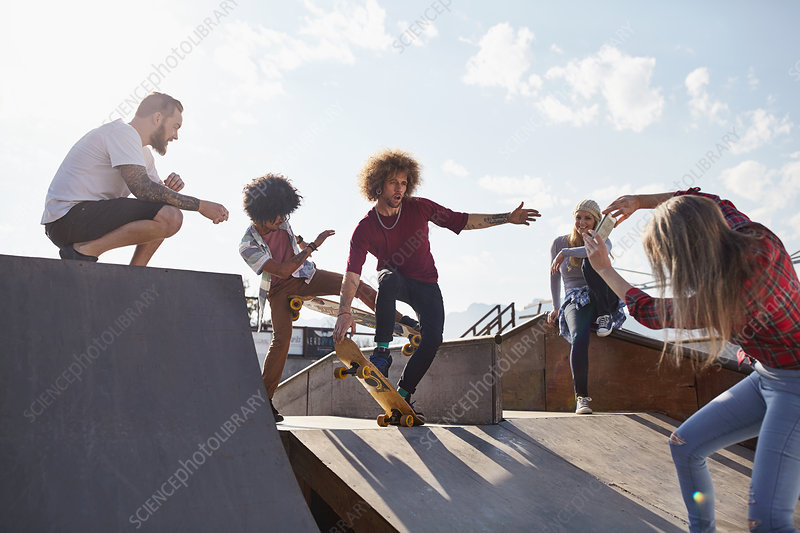 Woman photographing male friends skateboarding