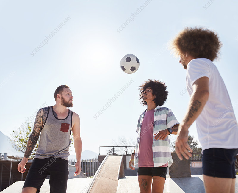 Male friends playing soccer