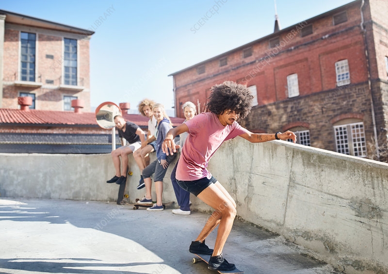 Friends watching man skateboarding on rooftop