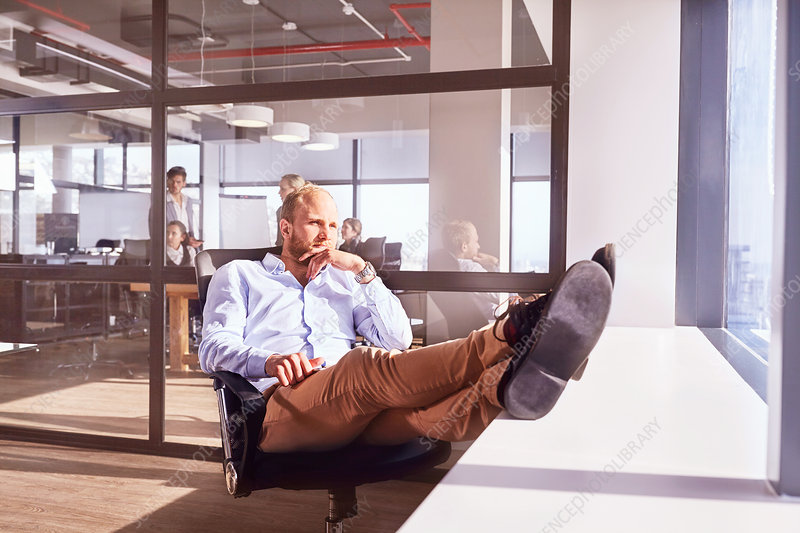 Pensive businessman sitting with feet up
