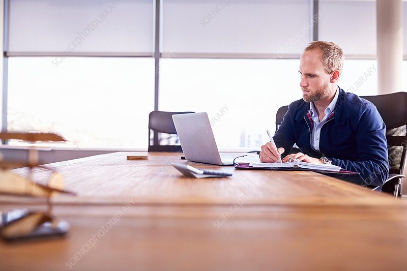 Focused businessman taking notes at laptop