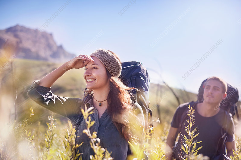 Smiling couple with backpacks hiking in field