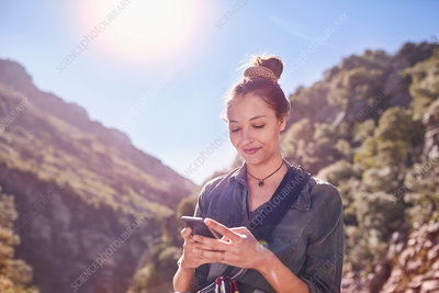 Young woman texting with cell phone below cliffs