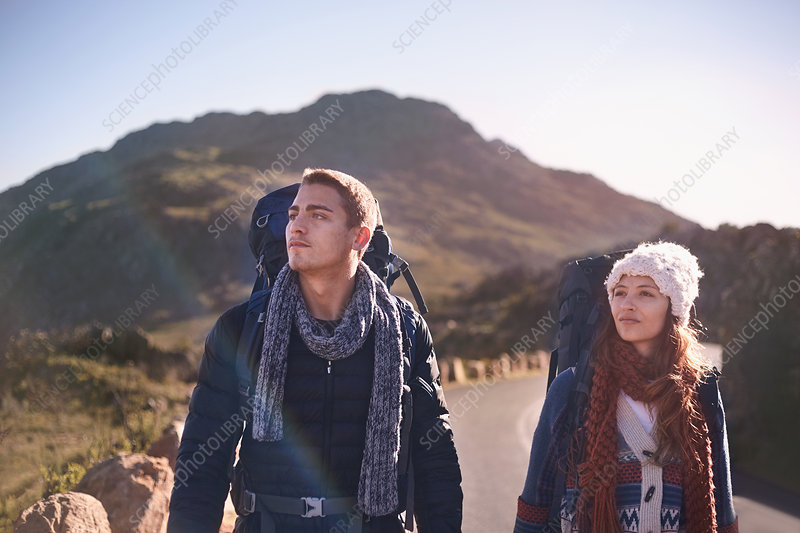 Young couple with backpacks hiking on remote, road