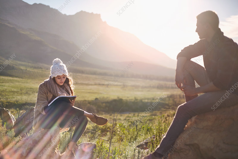 Young couple hiking, resting and writing