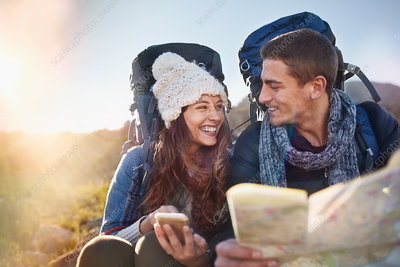 Young couple with backpacks hiking checking map