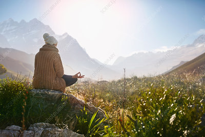 Young woman meditating on rock in, remote valley