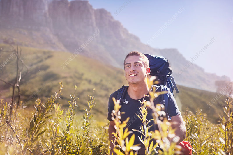 Young man with backpack hiking in valley