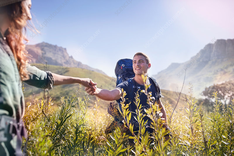 Young couple holding hands hiking in valley