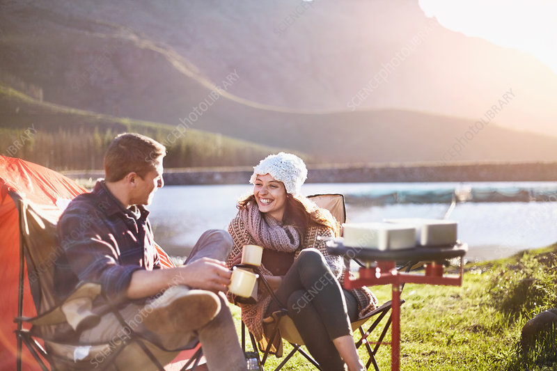 Young couple drinking coffee at lakeside campsite