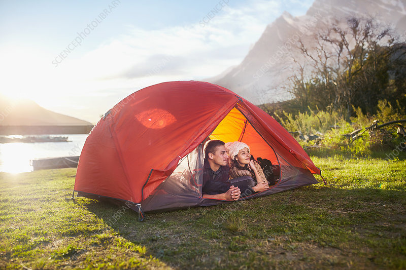 Young couple relaxing in tent at lakeside campsite