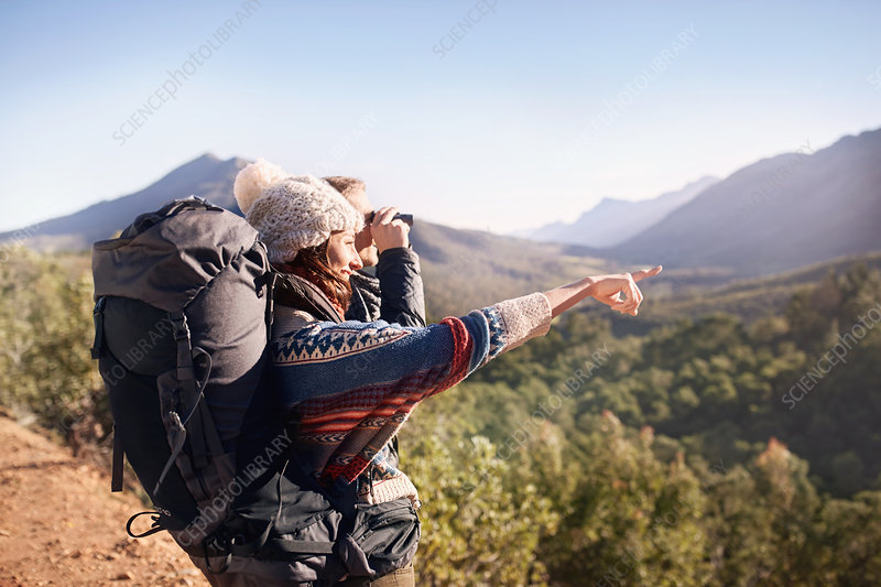 Young couple hiking, looking at view
