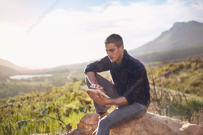 Young man using tablet on rock