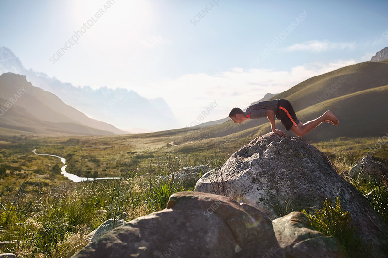 Young man balancing on hands on rock