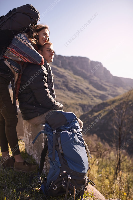 Young couple with backpacks looking at view