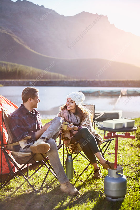 Young couple camping, drinking coffee