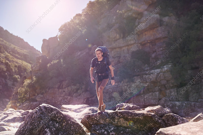 Young man with backpack hiking over rocks