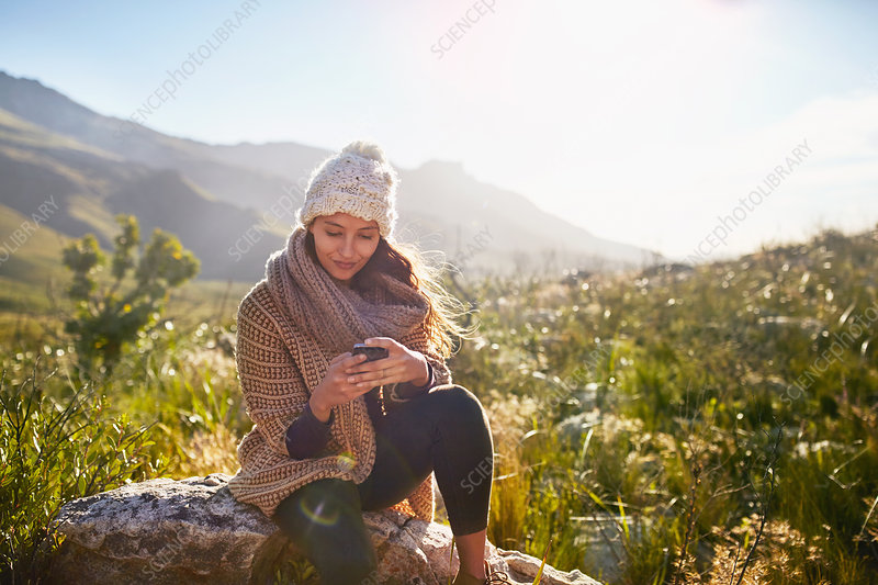 Young woman texting with cell phone on rock
