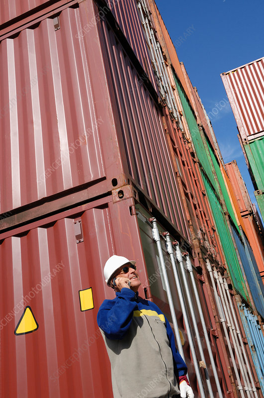 Industrial worker on cell phone with cargo containers