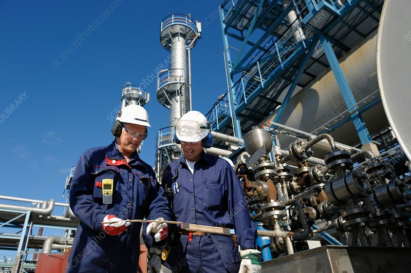 Oil refinery workers and pipework