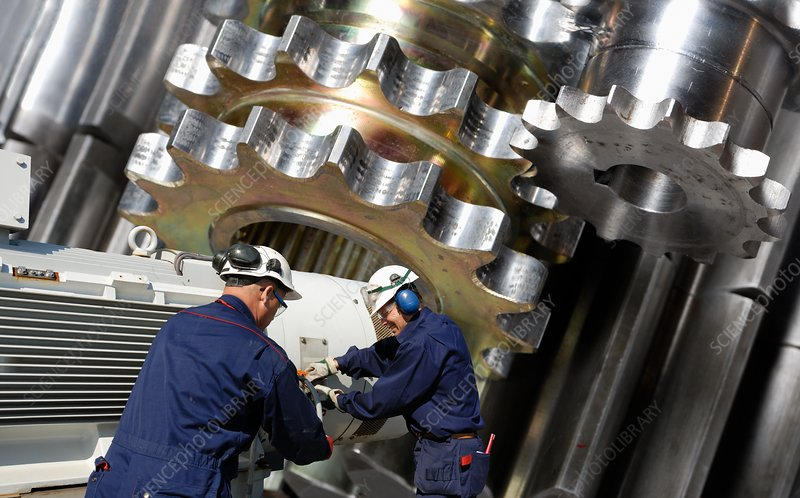 Engineers working with metal cogs