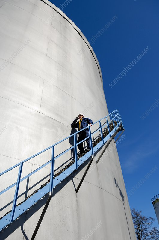 Man walking down steps on oil storage tower