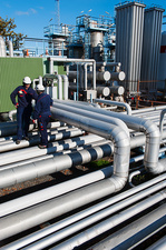 Workers checking pipework on an oil and gas refinery
