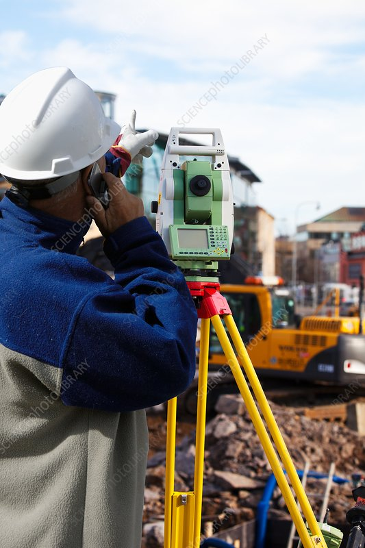 Surveyor using theodolite on construction site