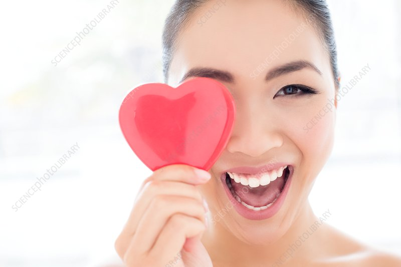 Woman covering eye with heart