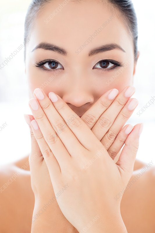 Woman with hands touching covering mouth