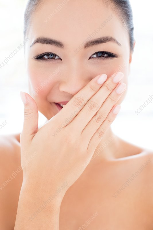 Woman laughing with hand covering mouth