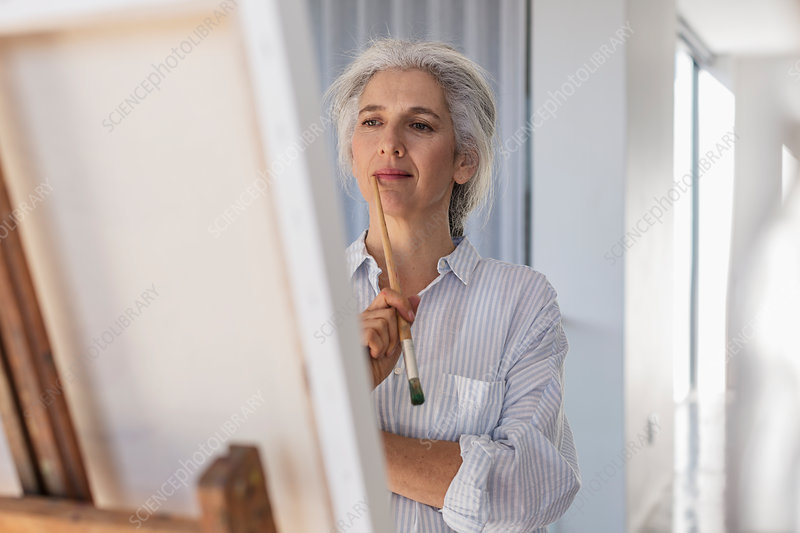 Pensive mature woman painting at easel
