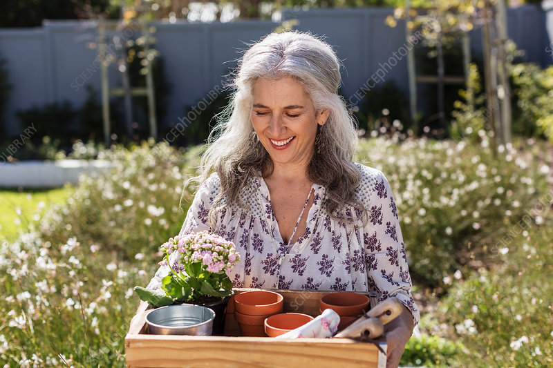 Smiling mature woman carrying gardening tray