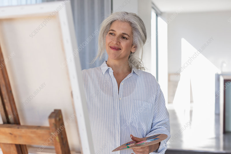 Smiling mature woman with palette painting