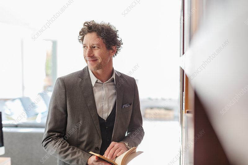 Smiling businessman reading book and looking away