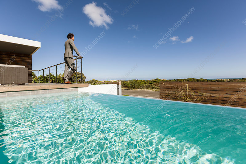 Businessman standing on patio with infinity pool