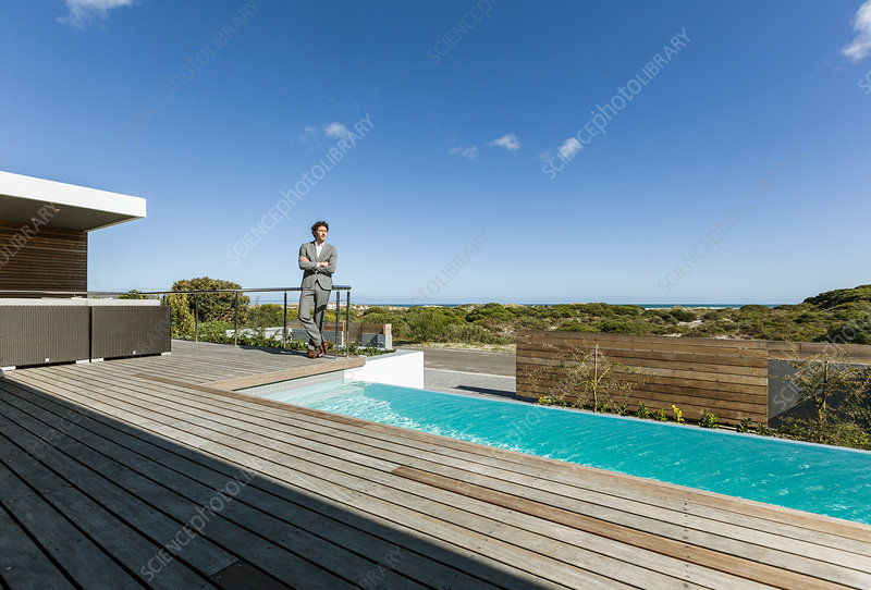 Businessman on patio with infinity pool