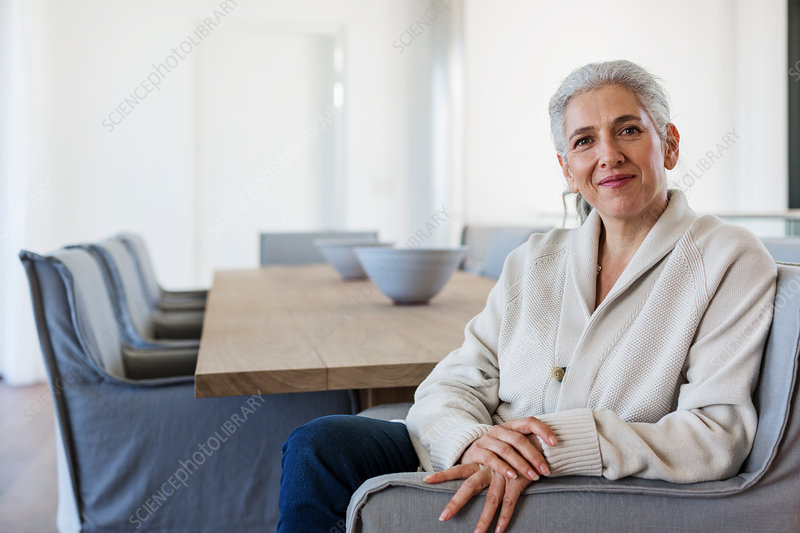 Portrait mature woman sitting at dining table