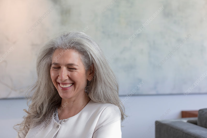 Mature woman laughing with eyes closed
