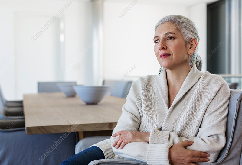 Mature woman at dining table looking away
