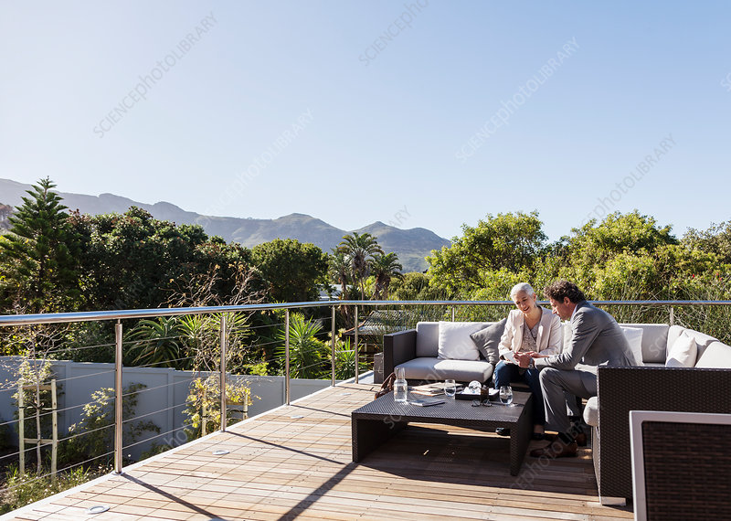 Businessman and businesswoman working on patio