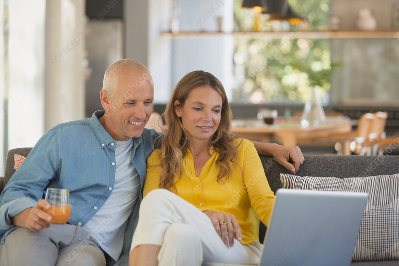 Couple relaxing, using laptop on living room sofa