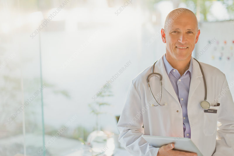 Portrait confident male doctor with digital tablet